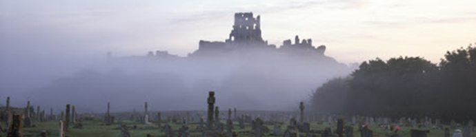 Corfe Castle from the South seen through dawn mist. This is one of Britain's most magnificent ruins and can be seen here with a graveyard in the foreground.